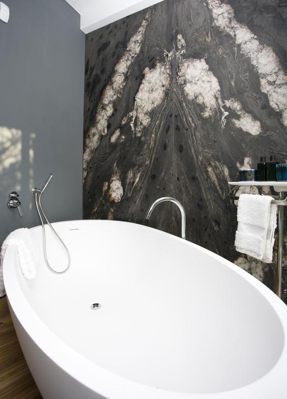 rivestimento bagno in marmo con vasca in pietra e pavimento in legno