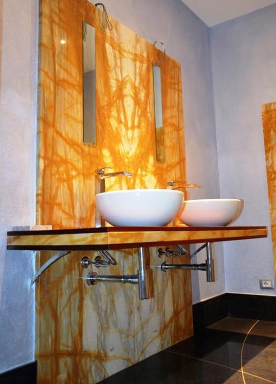 bagno con parete in marmo e lavabo appoggiato al top